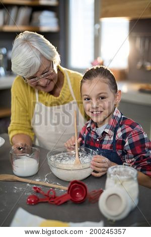 Granddaughter mixing flour in a bowl in the kitchen