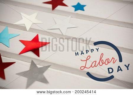 Digital composite image of happy labor day text with blue outline against star shape decorations on table