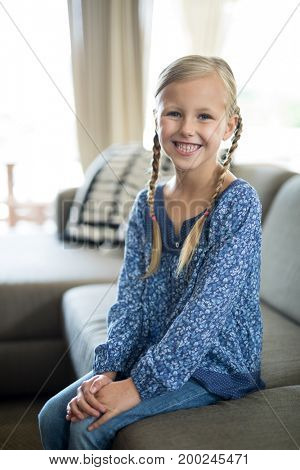 Portrait of smiling girl sitting on sofa in living room at home