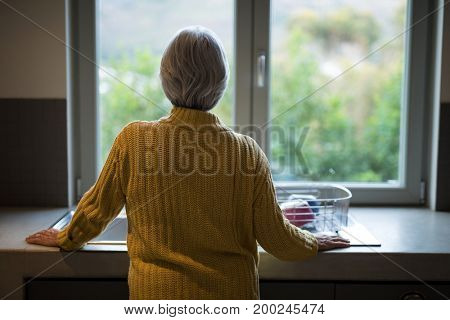 Rear view of senior woman standing near the kitchen sink and looking through window