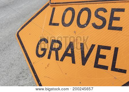 Loose gravel sign as shown in front of pavement