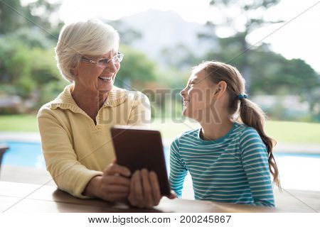 Laughing grandmother and granddaughter talking over a digital tablet near the pool
