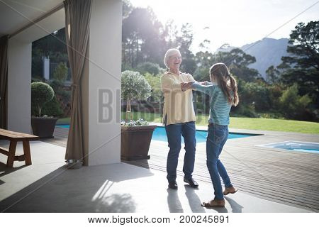 Happy granddaughter and grandmother holding their hands near the pool