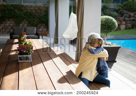 Granddaughter and grandmother embracing in a deck shade on a sunny day