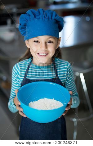 Close-up of smiling girl holding a bowl of flour in the kitchen
