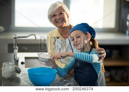 Grandmother posing with granddaughter sieving the flour in the kitchen