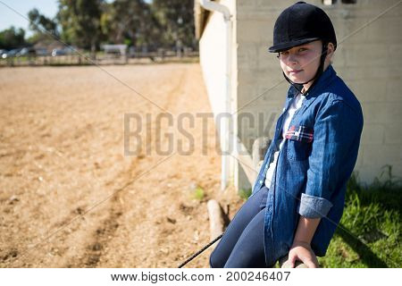 Portrait of girl leaning on wooden fence in the ranch