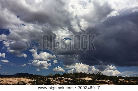 Large storm clouds with bright sun shining through onto vast wilderness landscape.