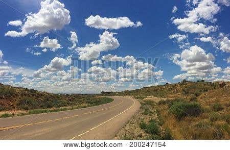 Country road headed into heavenly blue sky with puffy white clouds.