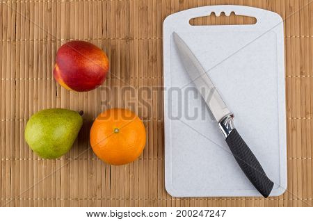 Tangerine, Pear, Nectarine, Cutting Board And Knife On Bamboo Mat