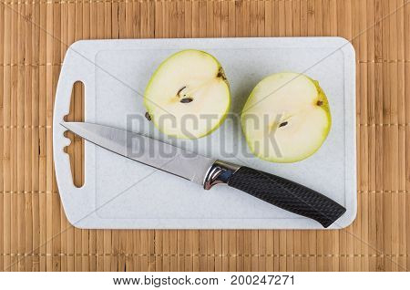 Two Half Of Pear And Knife On Cutting Board