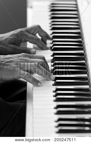 Closeup hands of musician pianist playing a piano. Shallow focus. Black and white.