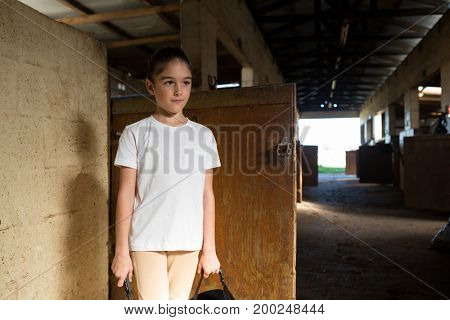 Thoughtful girl standing in stable