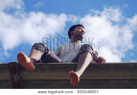young man sitting barefoot vacation summer low angle view blue sky