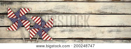 3D image of pinwheel toy with American flag pattern against wood panels in row