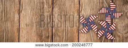 3D image of pinwheel toy with American flag pattern against close-up of wooden texture