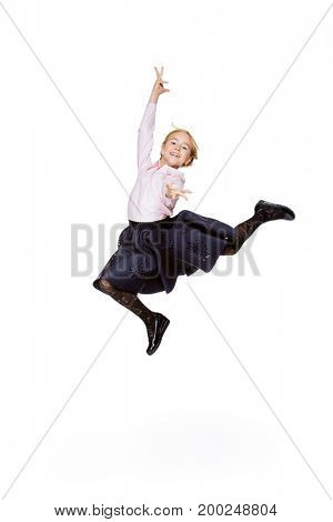 Happy excited schoolgirl in school uniform jumping for joy. Isolated over white background. School fashion. Copy space.