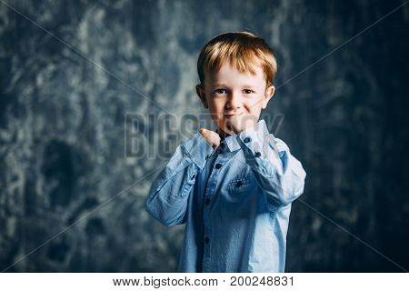 Little fighter. A five-year-old boy stands clenching his fists.