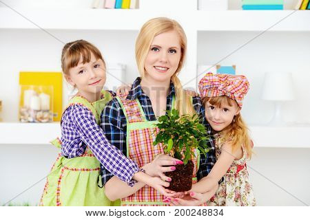 Happy loving family together. Little daughters help their mother to take care of plants at home.