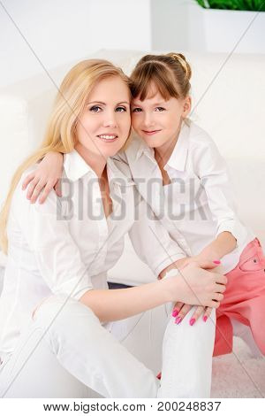 Happy family spending time together. Loving mother hugs her dear daughter.