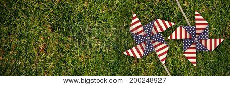 3D image composite of pinwheel with American flag pattern against full frame shot of grassy field