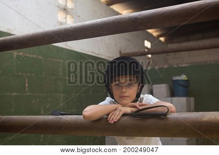 Portrait of cute girl leaning on rod in stable