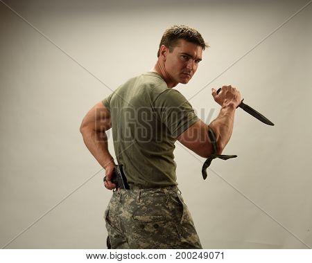 The strong army man is holding a dagger.