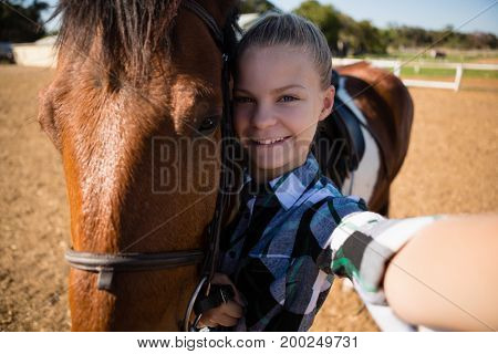 Girl taking a selfie with horse at the ranch