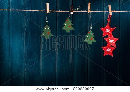 Blue Christmas background with red and green wooden christmas toys hanging on clothespin on grunge wooden wall. Xmas and New Year concept. Christmas or New Year card template with copy space.