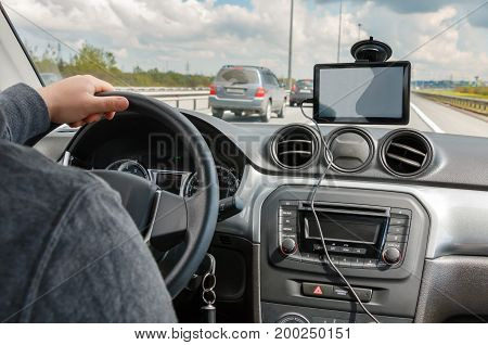 man driving car with hands on the steering wheel and using the portable GPS navigation