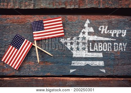 Composite image of happy labor day text and star shape American flag against two american flags on a wooden table