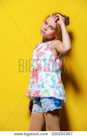 Bright summer girl. Cute eight-year-old girl in summer clothes posing over yellow background.
