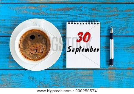 September 30th. Day 30 of month, loose-leaf calendar and hot cacao cup at translator or interpreter workplace background. Autumn time. Empty space for text.