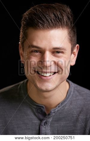 Smiling young white man looking to camera, vertical portrait