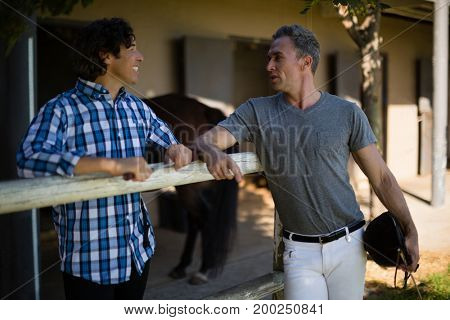 Two male friends interacting with each other in the ranch on a sunny day