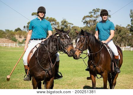 Two male jockeys riding horse in the ranch on a sunny day