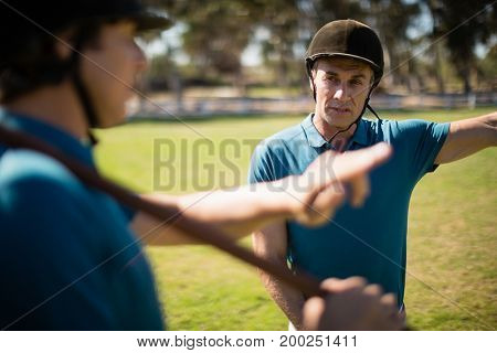 Tow male jockey talking to each other in the ranch