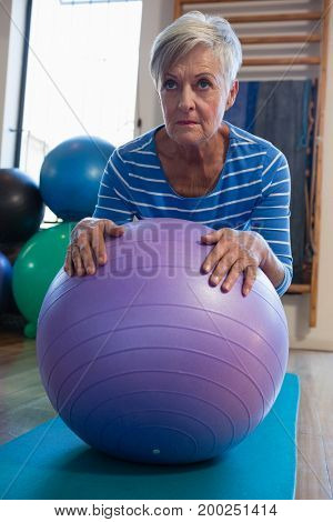 Senior woman in performing exercise on fitness ball at clinic