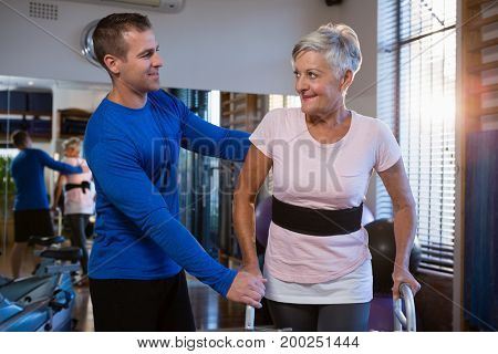 Man helping senior woman to walk with walker in hospital