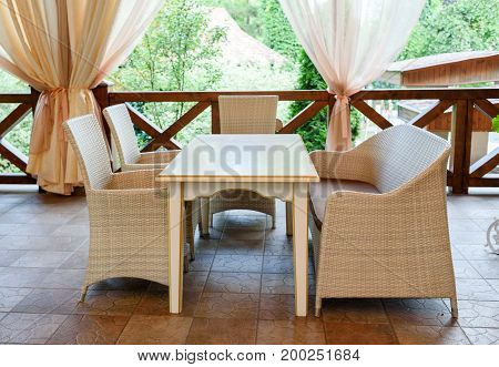 Empty Cafe With Rattan Wicker Armchairs And Table On Summer Garden Terrace Outdoor, Free Space. Tabl