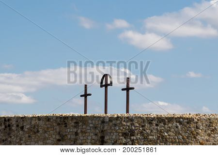 three crosses on hill on blue sky with clouds