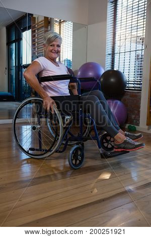 Portrait of smiling senior woman on wheelchair in clinic