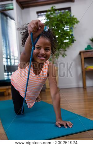 Smiling girl performing exercise on exercise mat in clinic