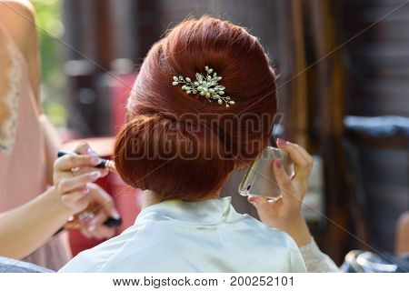 Back View Of  Beautiful Bride Talking By Mobile Phone While Makeup Artist Preparing Her Before Weddi