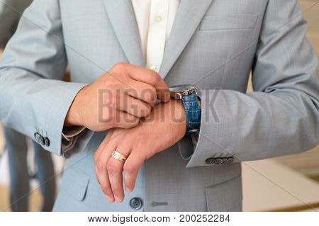 Closeup Watch On Businessman Hand. Watch On The Wrist Of Man In Gray Suit. Businessman Checking Time