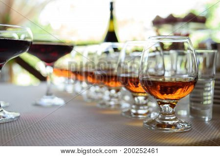 Row Of Glasses With Whiskey Or Cognac On The Table, Free Space. Strong Alcohol In Bar Or Restaurant.