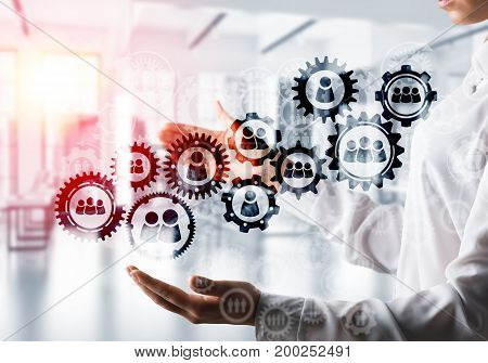 Business woman in white shirt keeping black social gear icons in hands with office view and sunlight on background. Mixed media.