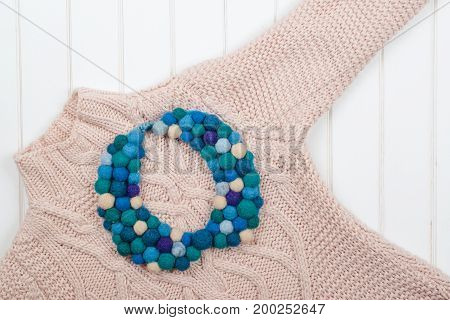 Felted Wool Necklace And Knitted Sweater On Wooden Background.