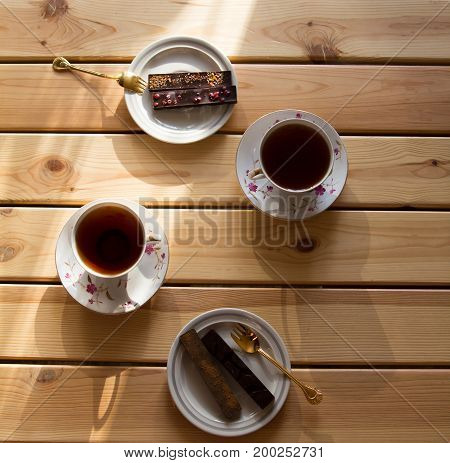 cup of tea and chocolate on wooden table lit by the sun. Top view. Close-up.
