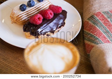 Cappuccino and cake with berries on table. Closeup. Top view.